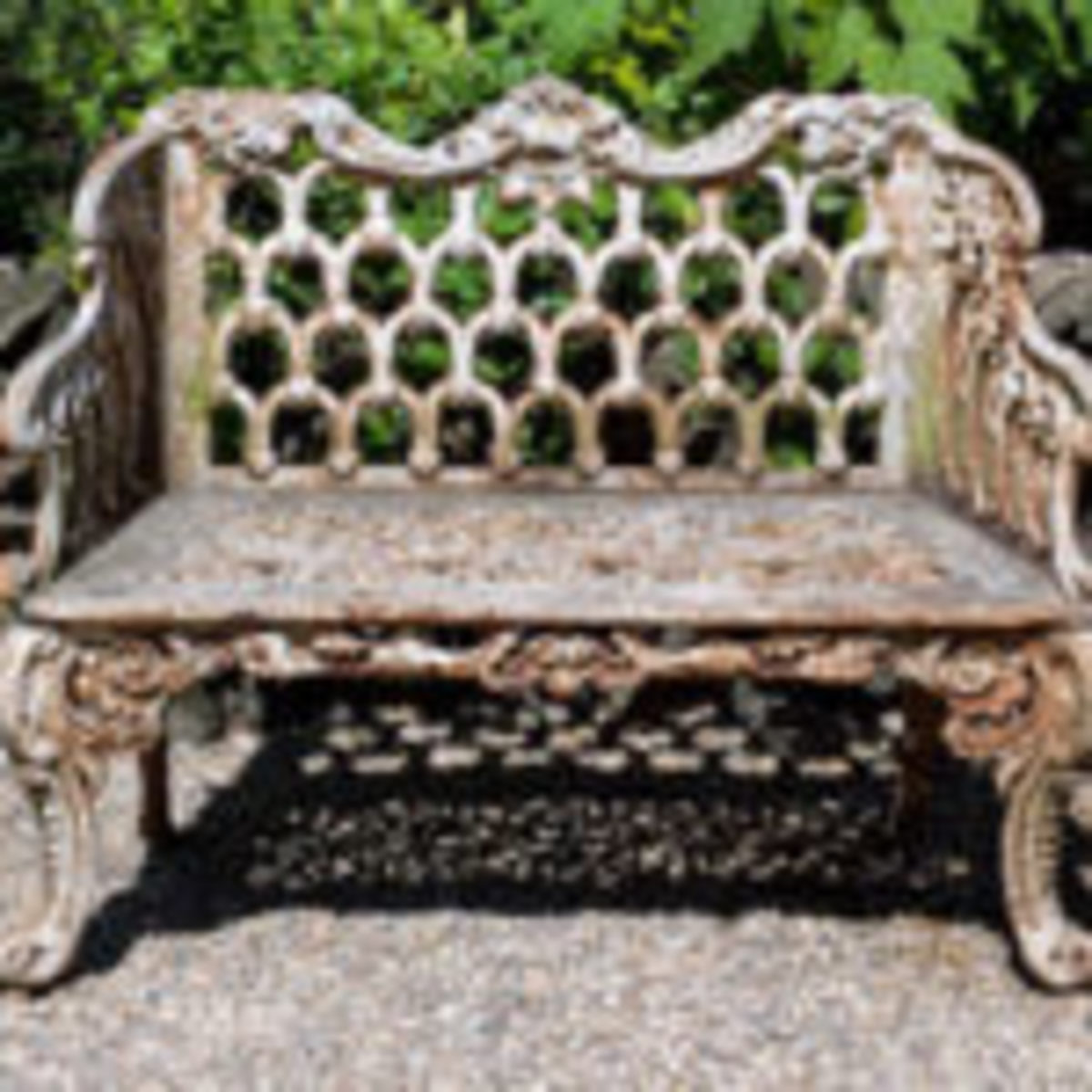 A small cast iron garden seat for two in the Rococo style. English, mid to late 20th century.