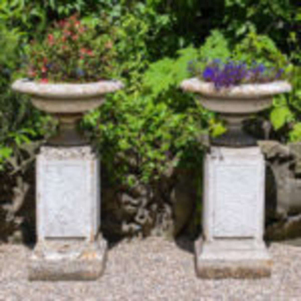 A pair of cast iron campana style urns on integral plinths, the shallow wide brimmed lobbed bowls above waisted socles, the stepped plinths with impressed crazed patterning. English, 1870s.