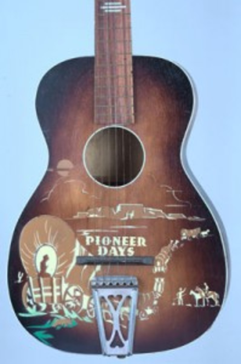 """""""Pioneer Days"""" guitar, 1951; artwork shows a wagon train with mountains, clouds and a distant sunset. This shaded brown finish guitar was made of birch, a wood often used for making cowboy guitars. (Photo courtesy Steve Evans)"""