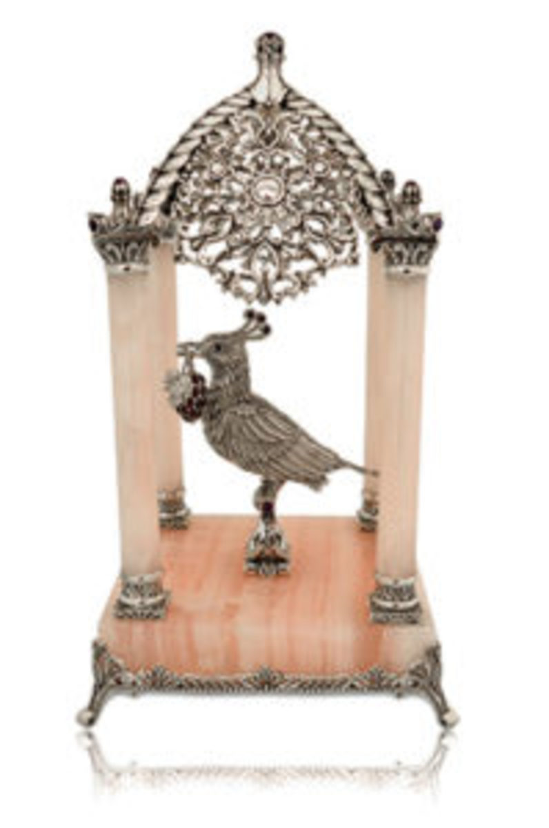 Exquisite, highly detailed, handcrafted sterling, jewel-crested silver bird perched within pink onyx gazebo. Courtesy www.nadavart.com