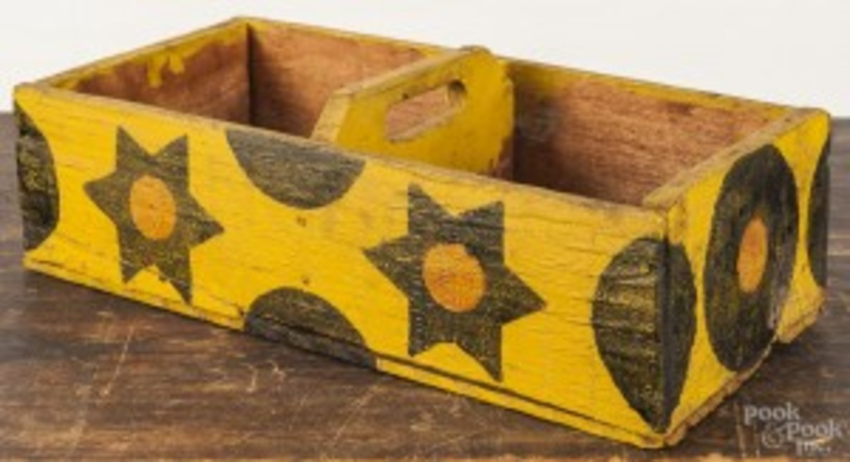 Painted pine carrier, 20th c., made from a shipping crate, with star and moon decoration on a yellow background, 4'' h., 15'' w., has a presale estimate of $150 to $200. (Photo courtesy Pook & Pook).