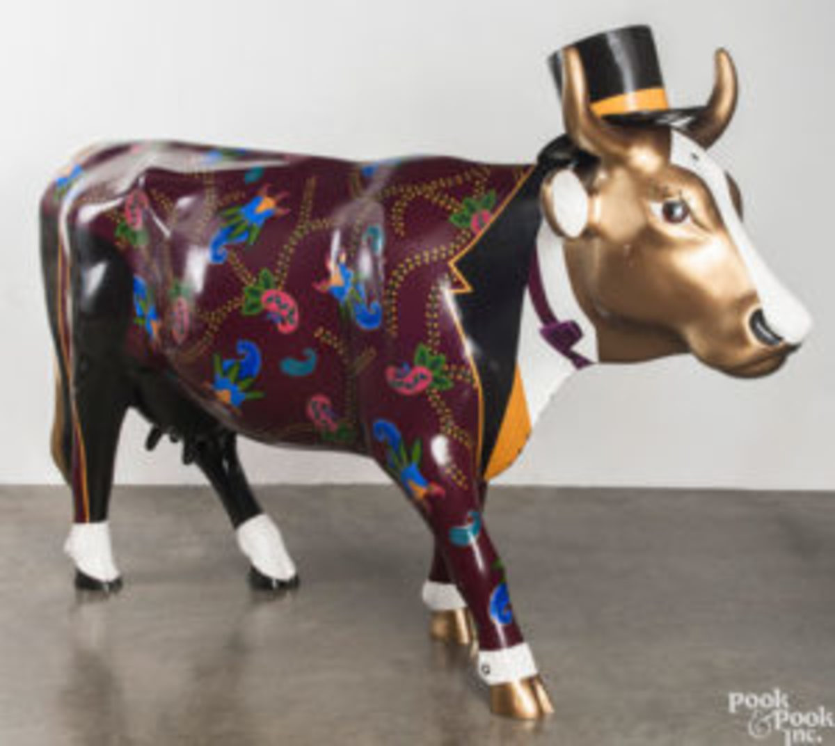 Life-size ceramic cow in a top hat