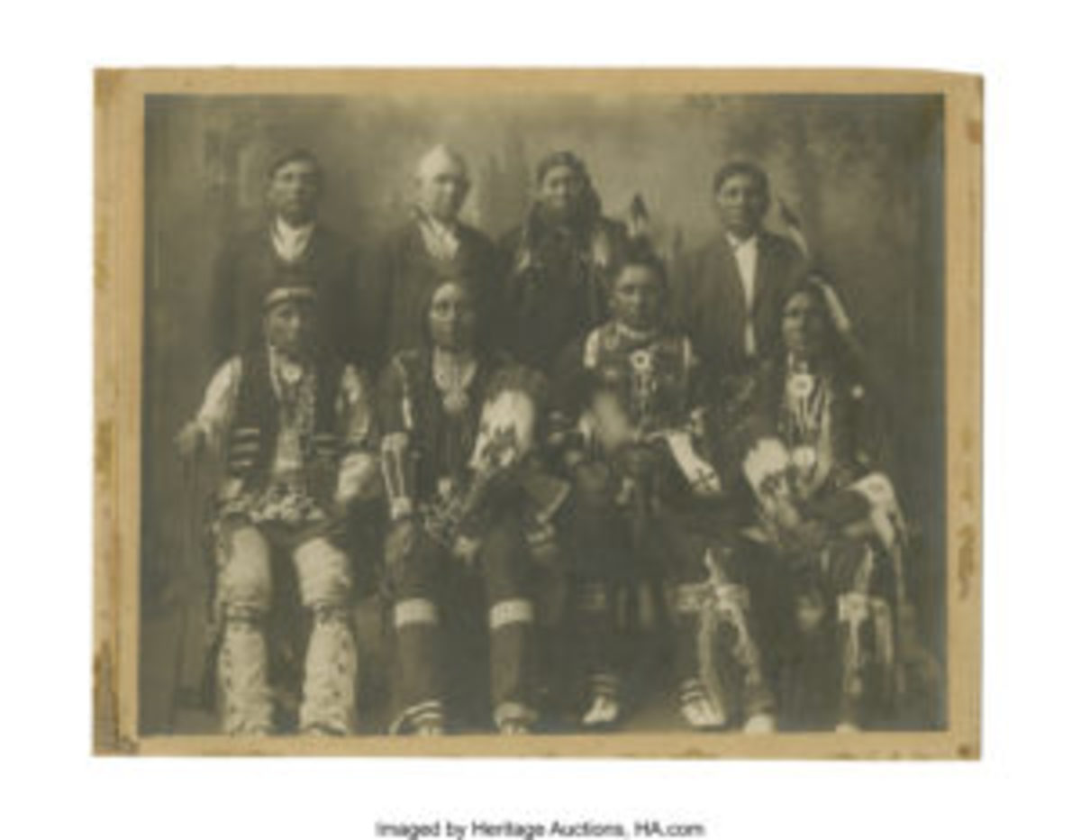 A photograph of Nez Perce Indian chiefs wearing Peace Medals, ca. 1890s. Depicts seven prominent Nez Perce/Umatilla Indian Chiefs posing for this historic photograph. Two of these Indians are wearing peace medals, four of them are displaying their fancy dress in an unidentified photographers' studio, and three are also wearing white man's clothing (there is also a white man standing with them in background). Pencil identification verso: Forest Chauteau, A. R. Miller, Silas Conn, Albert Taylor, Little Fire, Jim Pepper, Jess Majhoe & Ray Manval.