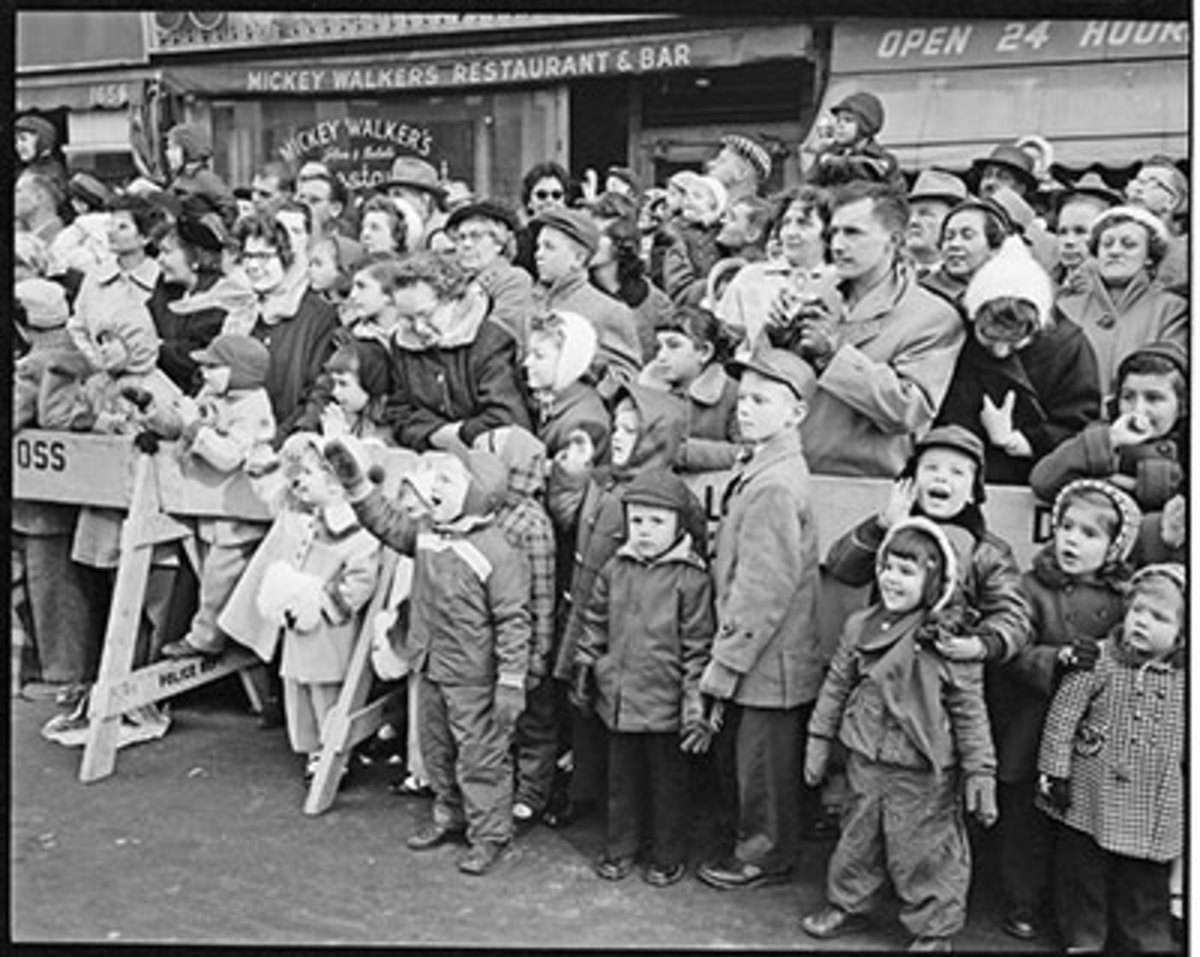 The crowd watching the 1956 parade behind a police barricade, with children watching in the front. Photo: Bettmann/Contributor/Getty
