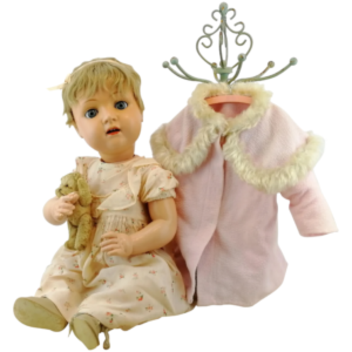 Large antique celluloid baby doll, 1908 to 1919, by Bruno Schmidt, Germany. She's wearing a dress of silky cotton with roses and for the colder days, she has a fancy pink coat with faux fur trim. She also has her own small and well-loved teddy bear; $275. Courtesy of Hildegard's Toy Emporium: rubylane.com/shop/hildegards-toy-emporium