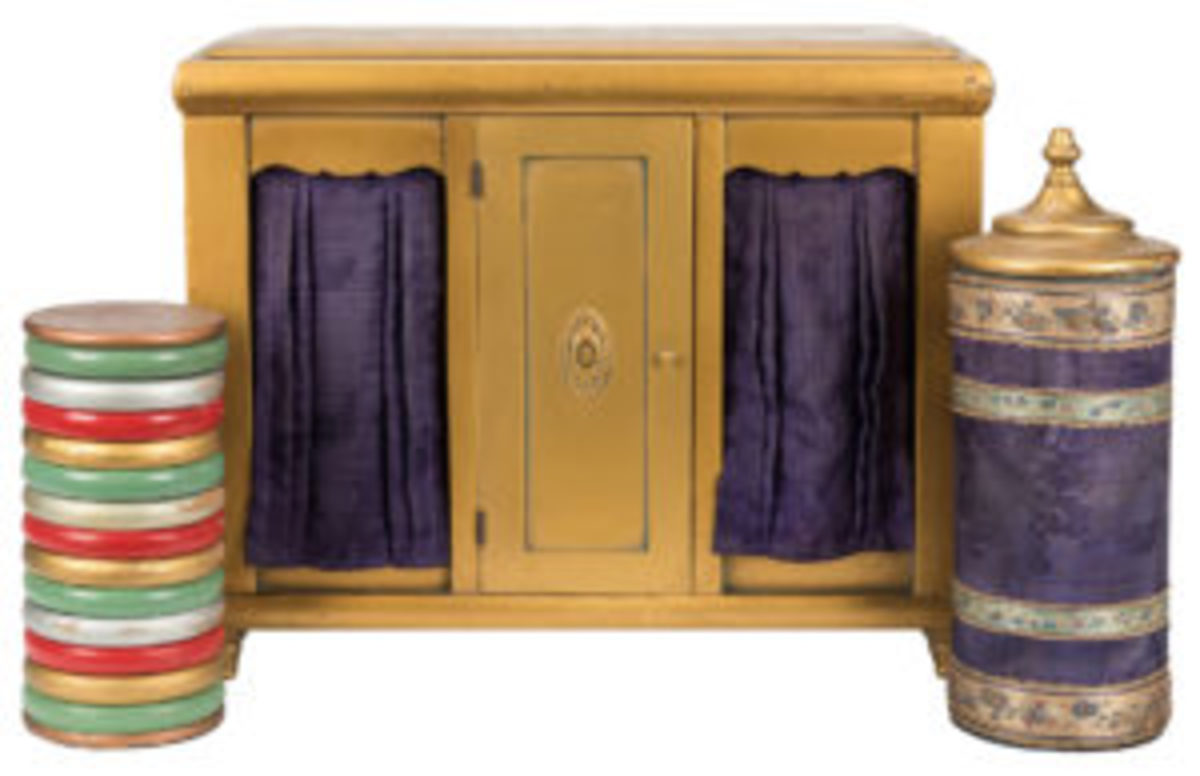 """W.J. """"Doc"""" Nixon checker cabinet, ca. 1925, sturdy wooden cabinet with two curtains at front finished in bright gold, accompanied by plush-covered cylinder bearing a turned wooden top, a stack of checkers and a glass tumbler transpose locations at the command of the magician, 17-1/2"""" x 15"""" x 7"""". Nixon's version of the Checker Cabinet effect popularized by Thayer and Okito, with purple curtains in the place of wooden doors, and including the appearance of water and goldfish in the tumbler placed in the cabinet, an interesting touch and refinement. Estimate: $1,500-$2,000."""