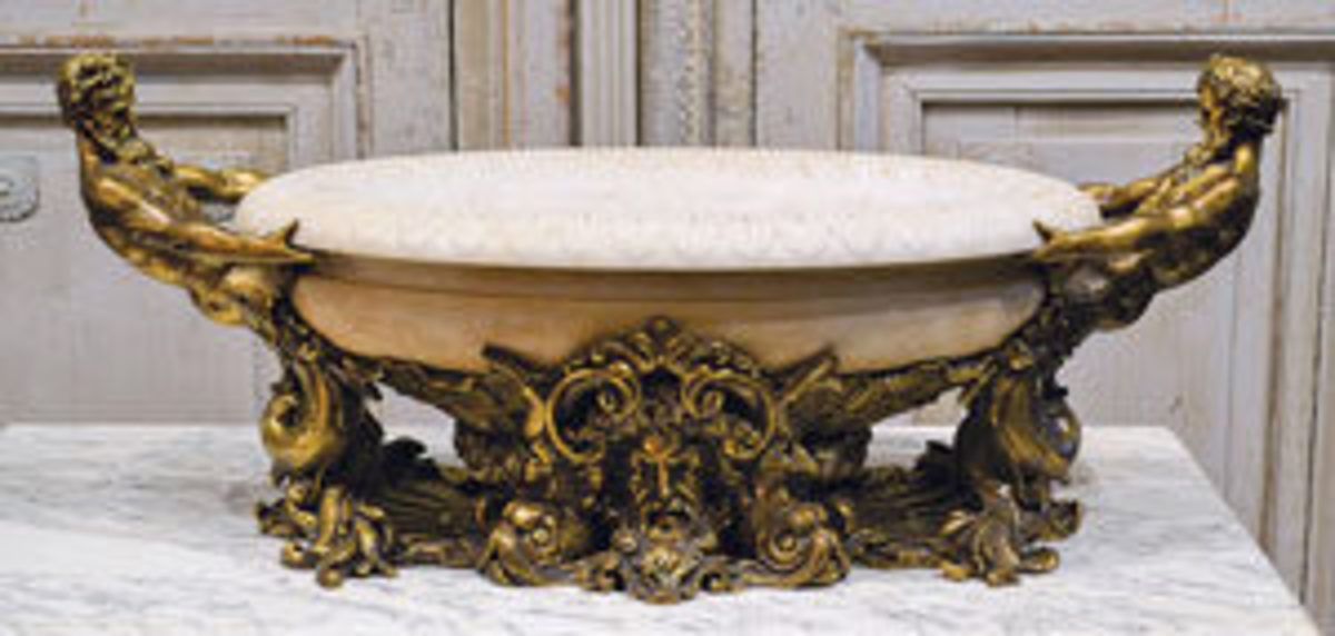 Large American gilt bronze and white marble centerpiece by Edward F. Caldwell & Co. (N.Y.), circa 1905, with the large marble bowl held by two Greco-Roman figures; estimate: $15,000-$30,000.