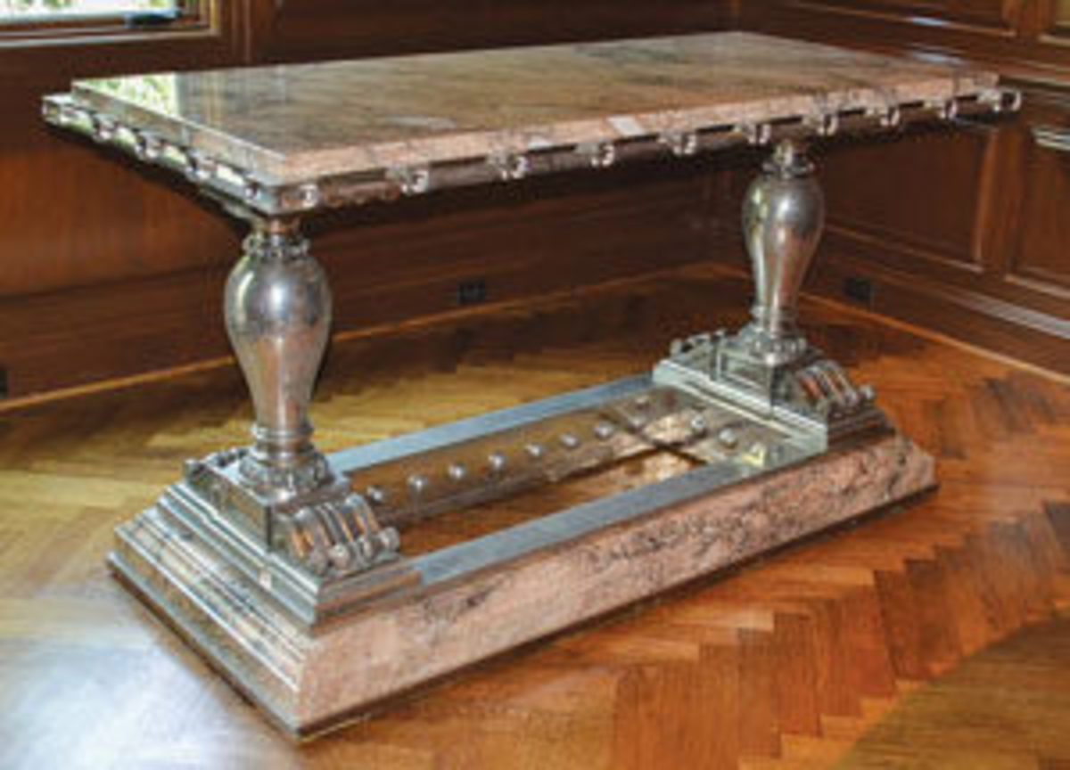 One of a monumental pair of palace tables from around 1890, polished nickel and steel with rouge marble tops, from a design by Charles Paxton Gremillion, 6 feet long; estimate: $25,000-$50,000.