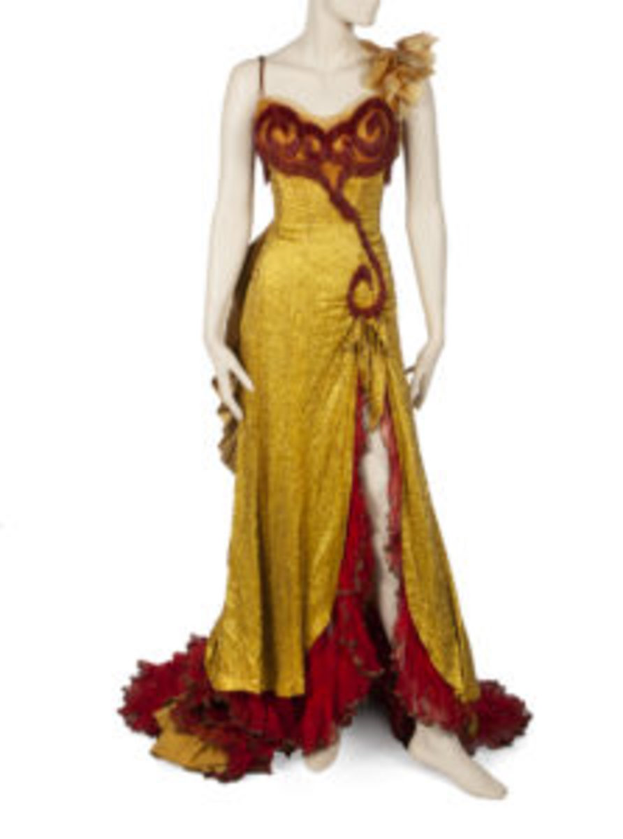Marilyn Monroe's period gown from River of No Return (20th Century Fox, 1954)sold for $175,000 (estimate was $60,000-$80,000). The bright yellow floor-length gown is made of silk and has spaghetti straps, with yellow silk flowers sewn to left strap, the bodice covered in gold bugle beads with additional red dangling bugle beads at bust, long front slit at left leg topped with a small bow, and attached petticoat made of multi-layered red tulle netting trimmed in gold metallic.
