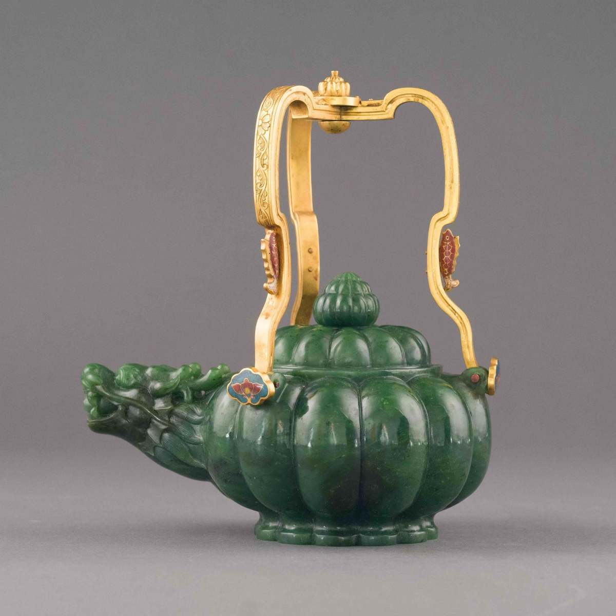 """Green jade gilt bronze-handle tea pot, 15th Century Ming Dynasty Period, China. In the shape of a plum, with gilt bronze tripod handle, inlaid in cloisonne, multi-lobed vessel, with convex spigot issuing forth into a small aperture. Crown-shaped lid partitioned into lobed sections, with lobed patterned finial. Each gilt bronze tripod arm is fashioned with a cloisonne encrusted lotus flower at the joint, followed midway up the arm by imperial dragon festoon. The main body carved in melon fruit shape, with the dome lid finial bud, with original box; 11"""" h, 8-3/4"""" w, $3,000."""
