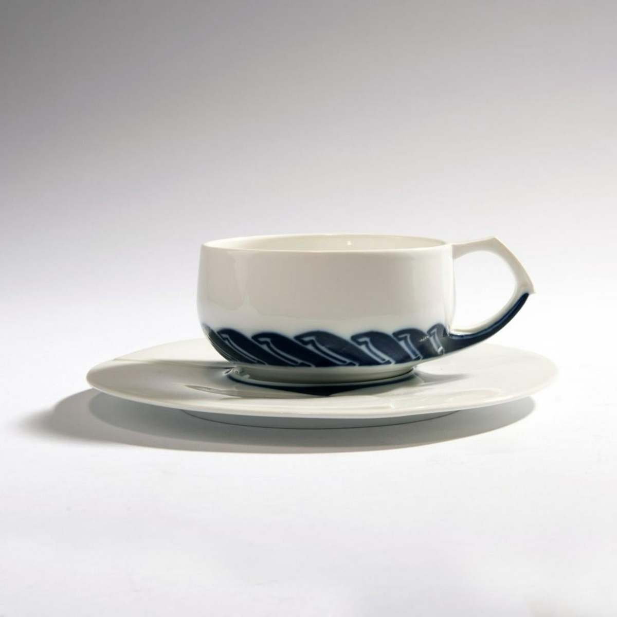 Henry van de Velde teacup and saucer, 1903/04, made by KPM Meissen before 1924, porcelain, relief, white, glazed, cobalt underglaze. Marked: Maker's mark, 71 (blue, under glaze, two strokes), artist's mark (embossed), $3,900.