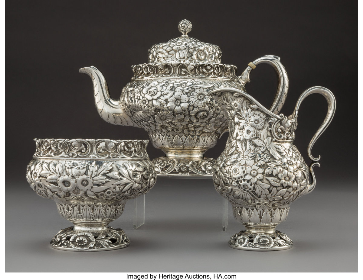 """A three-piece Tiffany & Co. floral repoussé tea service, New York, circa 1875, comprising 1 teapot with hinged lid, 1 creamer and 1 waste bowl. Marks:""""TIFFANY & CO, 3949T2990, STERLING,"""" 1-3/4 pints, 5 cups, 6-3/4"""" x 9-1/4"""" (tallest, teapot), $2,500."""