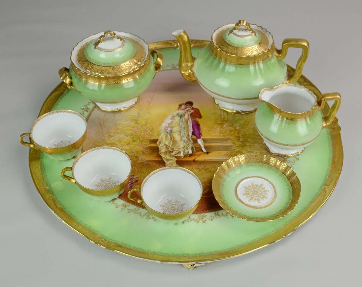"""Theo Haviland Limoges tea set, gilt highlighted green platter with romantic scene at center, teapot with gilt handle, spout and edge, coordinating cream and sugar, 3 cups, 1 saucer, platter is 17-1/2"""", $120."""