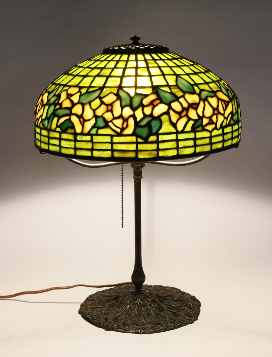 "Tiffany Studios Banded Dogwood table lamp, circa 1910, the leaded glass shade stamped, ""Tiffany Studios New York,"" on a Wild Carrot or Queen Anne Lace patina bronze base stamped, ""Tiffany Studios New York 325,"" shade is 5-1/4"" diameter, base height is 12-1/2"". Estimate: $10,000-$15,000."