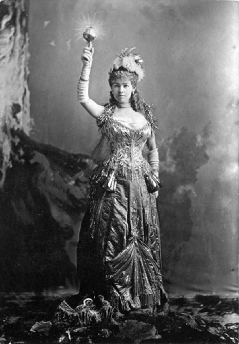 """Mrs. Cornelius Vanderbilt (Alice Claypoole Gwynne) as """"Electric Light"""" in a costume designed by Charles Frederick Worth. A built-in battery lit a light bulb she carried and could raise over her head like the Statue of Liberty."""