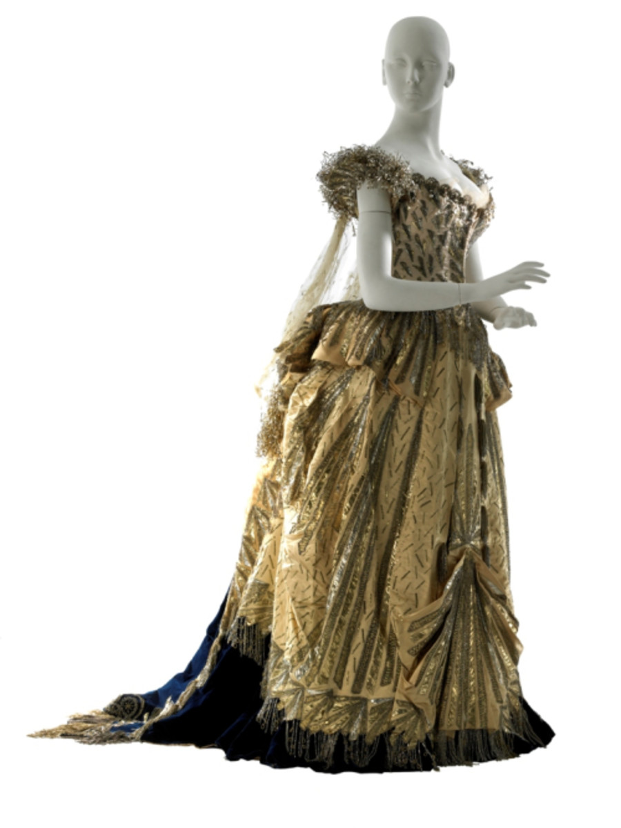 The yellow satin Electric Light dress designed by Charles Frederick Worth. It's decorated with glass pearls and beads in a lightning-bolt pattern. This dress was only one of several spectacular gowns that served to make the event the official start of Alva Vanderbilt's role as a leading socialite of New York. The dress is preserved at Museum of the City of New York.