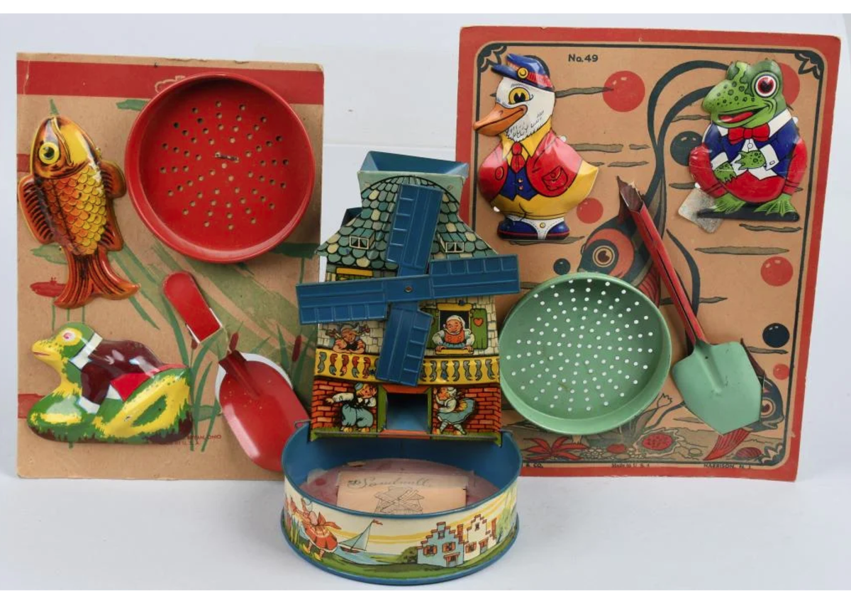 Three new old stock sand pail accessories including a tin sandmill with Dutch graphics, and two Chein tin toy accessories on cards; $200.