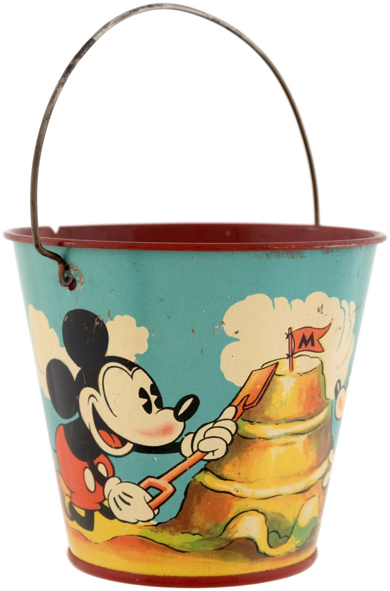 """A rare Happynak tin litho sand pail featuring Mickey and Minnie Mouse building a sand castle, 1930s. Of the numerous Disney sand pails made by Happynak of England, only a few were done in full color, including this one; 3-5/8"""" h (6-1/4"""" h to top of raised wire handle), $1,238."""