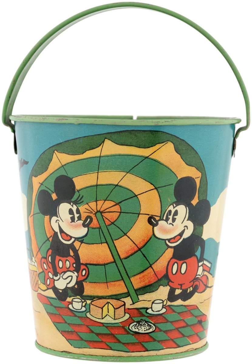 """This tin litho sand pail features nice wrap-around scene depicting Mickey and Minnie Mouse having picnic at the beach, with Pluto sitting by their side (shown below), Ohio Art, 1930s, 4-1/4"""" h (6-1/2"""" to top of raised handle), $240."""