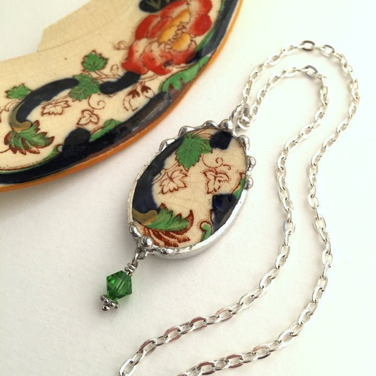 A broken china ivy leaf pendant necklace from antique Masons Ironstone in Mandalay Imari colors and a dangling green crystal.