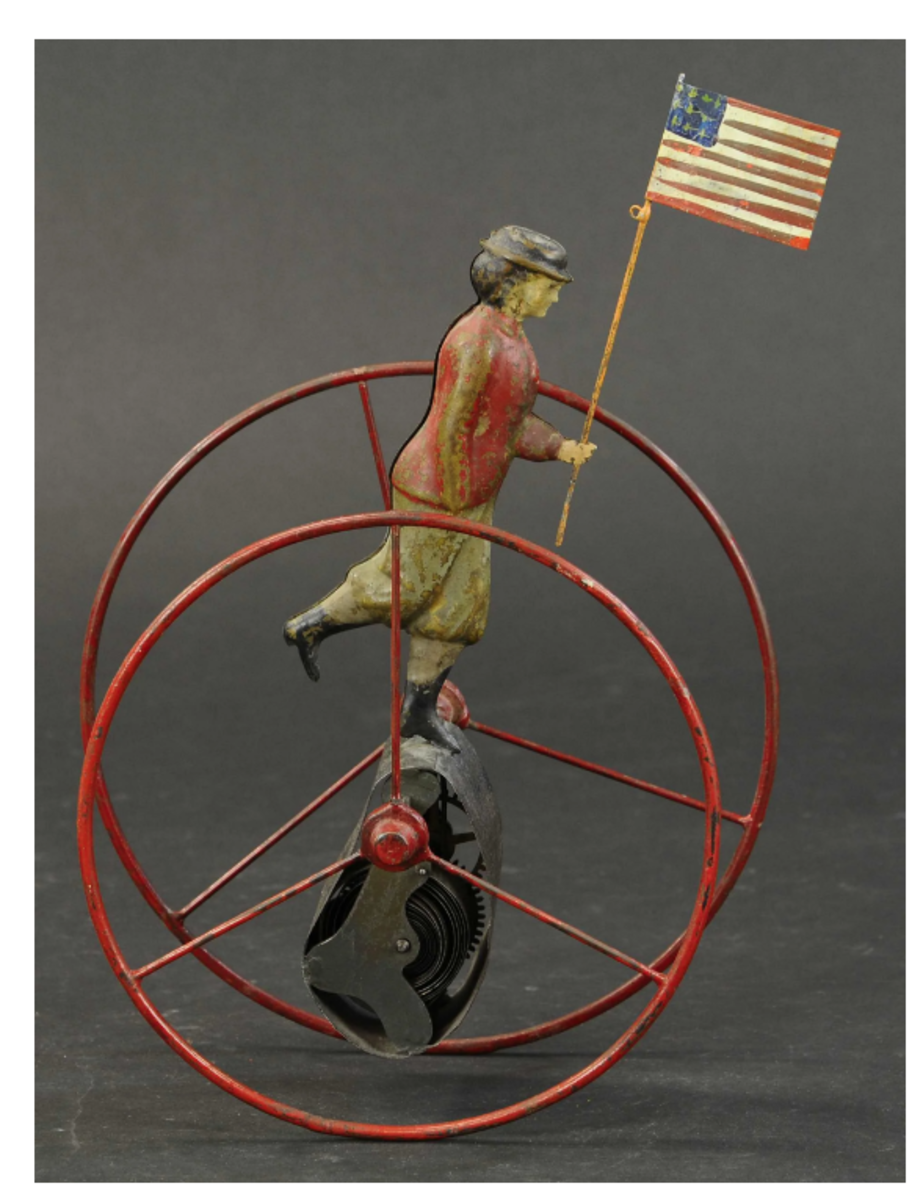 A rare and desirable toy of a suffragette in mechanical hoop, circa 1880s, by George Brown, the hand-painted tin figure stands on a covered clockwork mechanism, encircled by red hoop while holding a flag, $6,000.