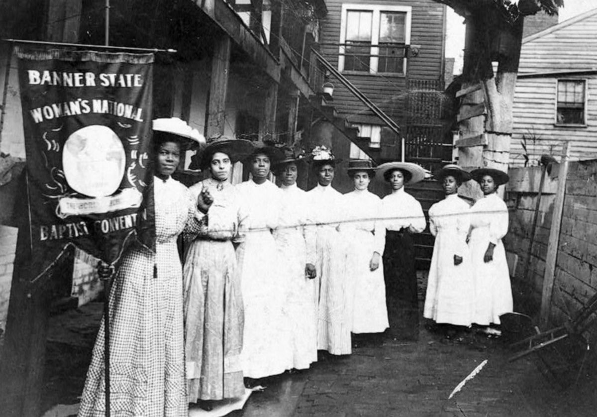 """Nine African-American suffragists pose for a photo with Nannie Burroughs, holding a banner that reads, """"Banner State Woman's National Baptist Convention,"""" circa 1905."""