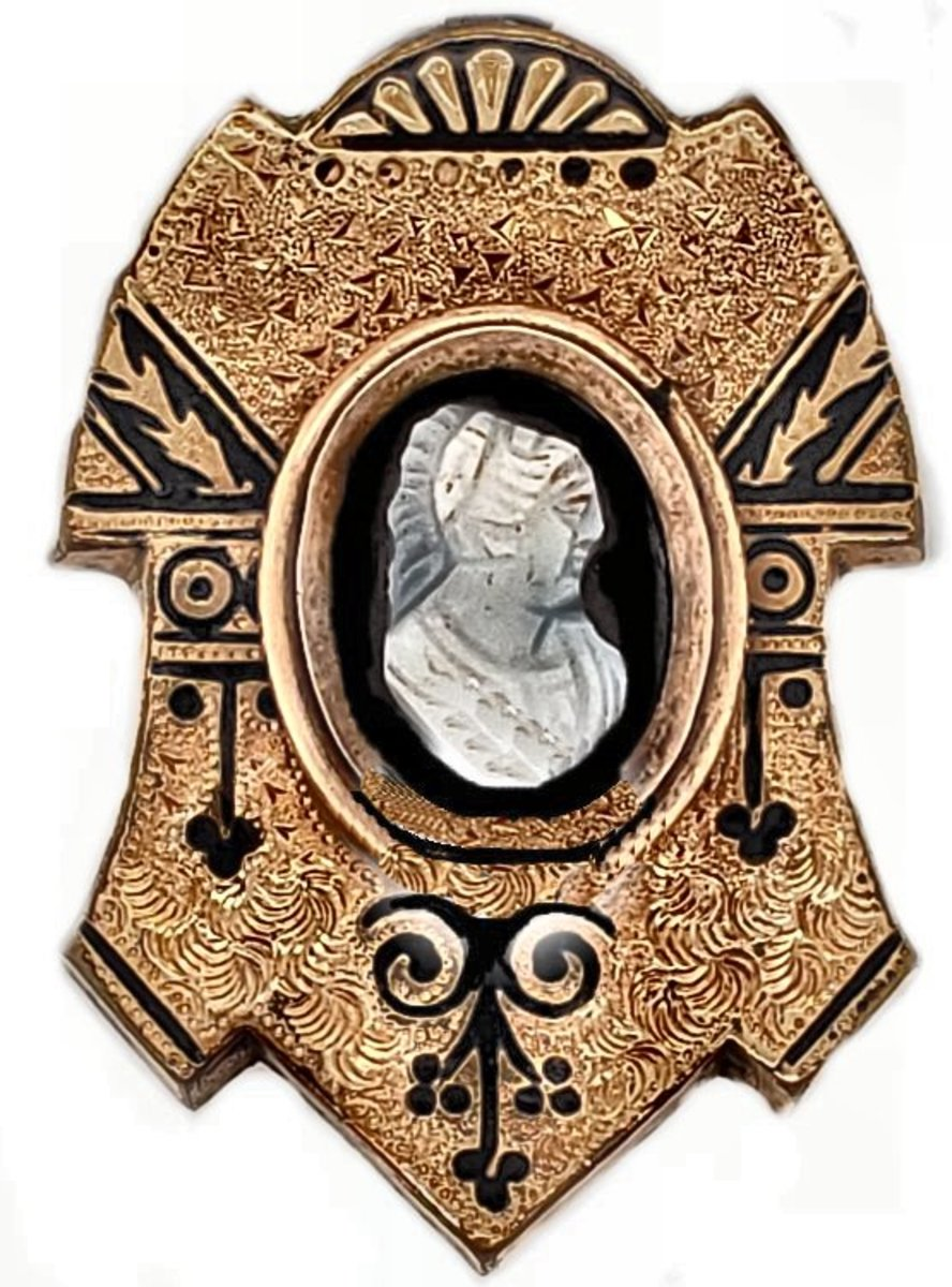 This appearance of this textured gold brooch with a hardstone cameo is greatly enhanced by the black enamel tracery seen in many mid-Victorian pieces of jewelry.
