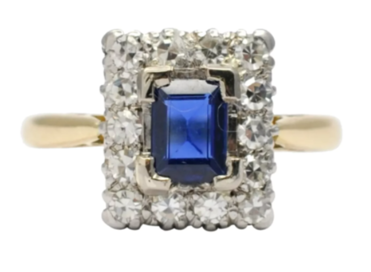Rectangular sapphire and diamond cluster engagement ring set in 18k gold and platinum, 1920. The deep royal blue sapphire weighs 0.50 carat and is surrounded by 8-cut diamonds totaling 0.42 carat; $1,100.