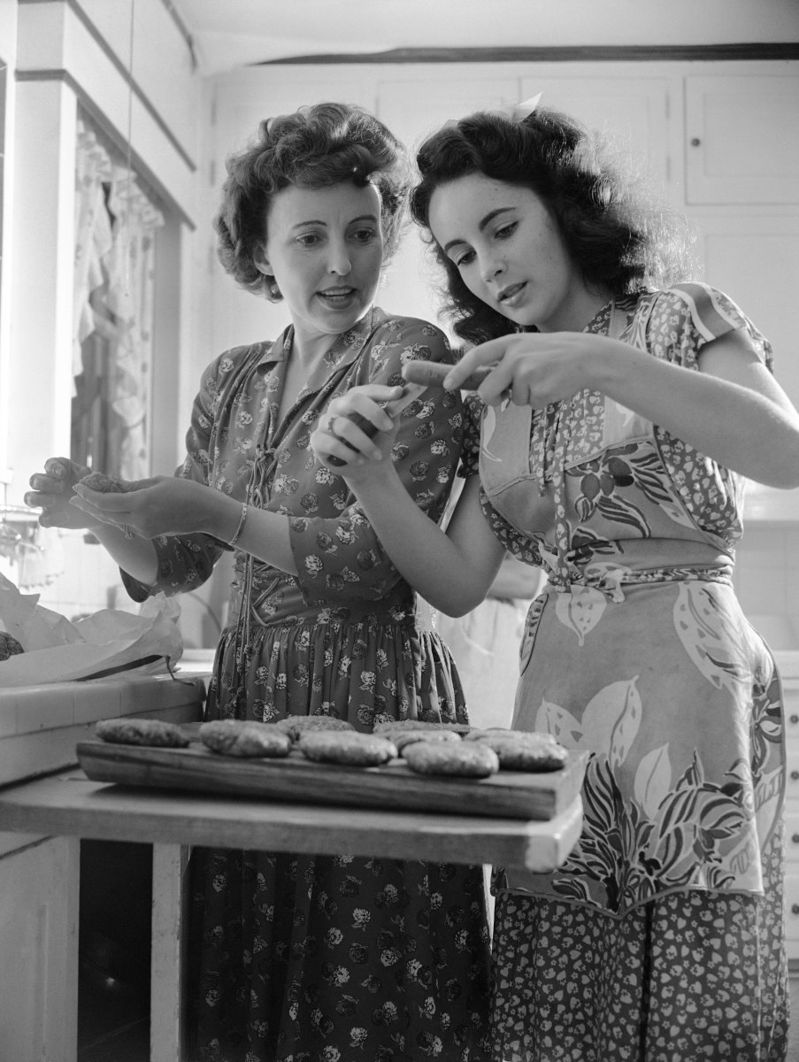 Actress Elizabeth Taylor helps her mother prepare hotdogs and hamburgers at home circa 1947 in Los Angeles, California.
