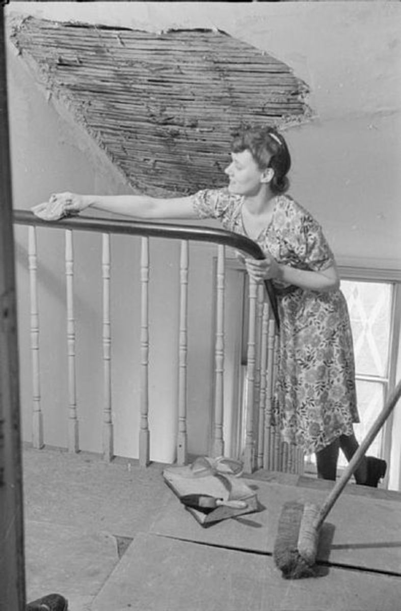 A day in the life of a wartime housewife, London, England, 1941: Mrs. Olive Day does some housework before she leaves for work. Here she is polishing the bannisters. The large patch of missing plaster on the ceiling above her head was caused by a nearby air raid.