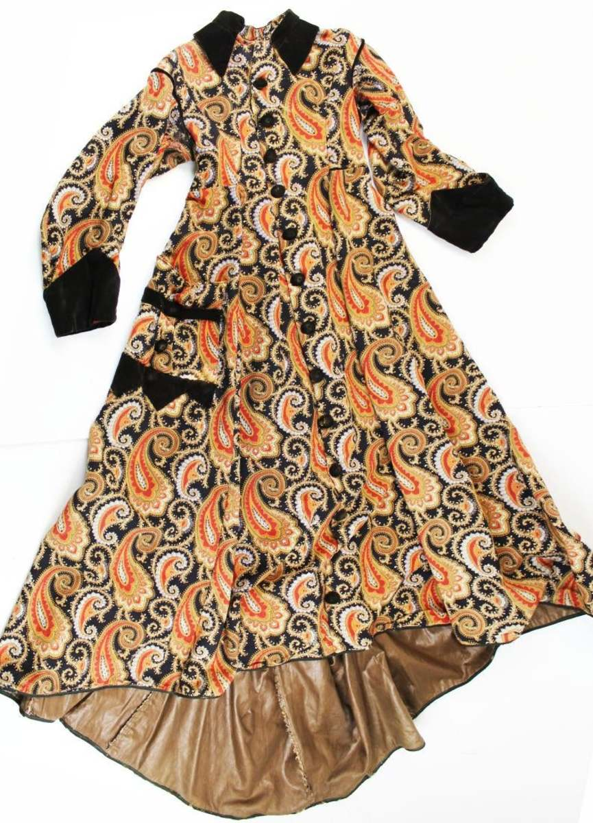 A 19th century Victorian vibrant paisley print wool house dress with full button front, dark brown velvet piping, collar and cuffs, large single pocket, and brown chintz lining; $275.