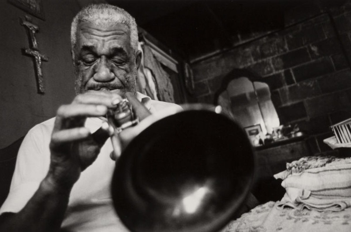 """DeDe Pierce, Blind Jazz Musician, Playing his Trumpet in his Bedroom, New Orleans, Louisiana,"" 1965. ""DeDe sat on the bed, his blind eyes to the window; he seemed to be reading the notes from somewhere out there. Then laying the instrument aside, he said, 'Yes, the old Jazz, the real blues, it had something to say.'"" Estimate: $1,500-$2,500."