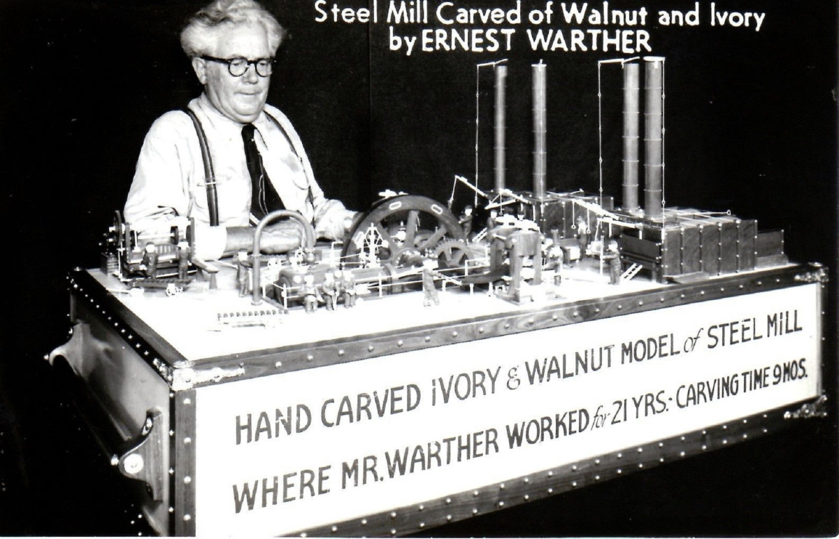 "Ernest ""Mooney"" Warther showing off his carved steel mill complex."