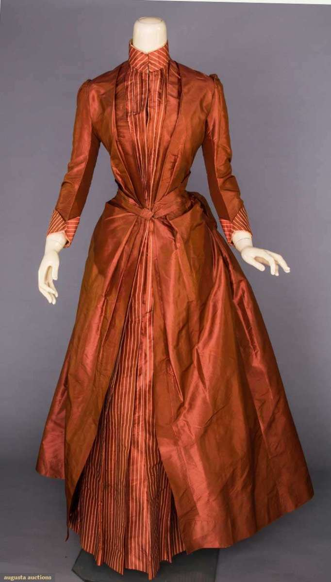 An 1880s' dress in copper silk taffeta, with a fitted bodice with floor-length polonaise and bustle back; the copper underskirt has pink pinstripes. This sold at auction for $480.
