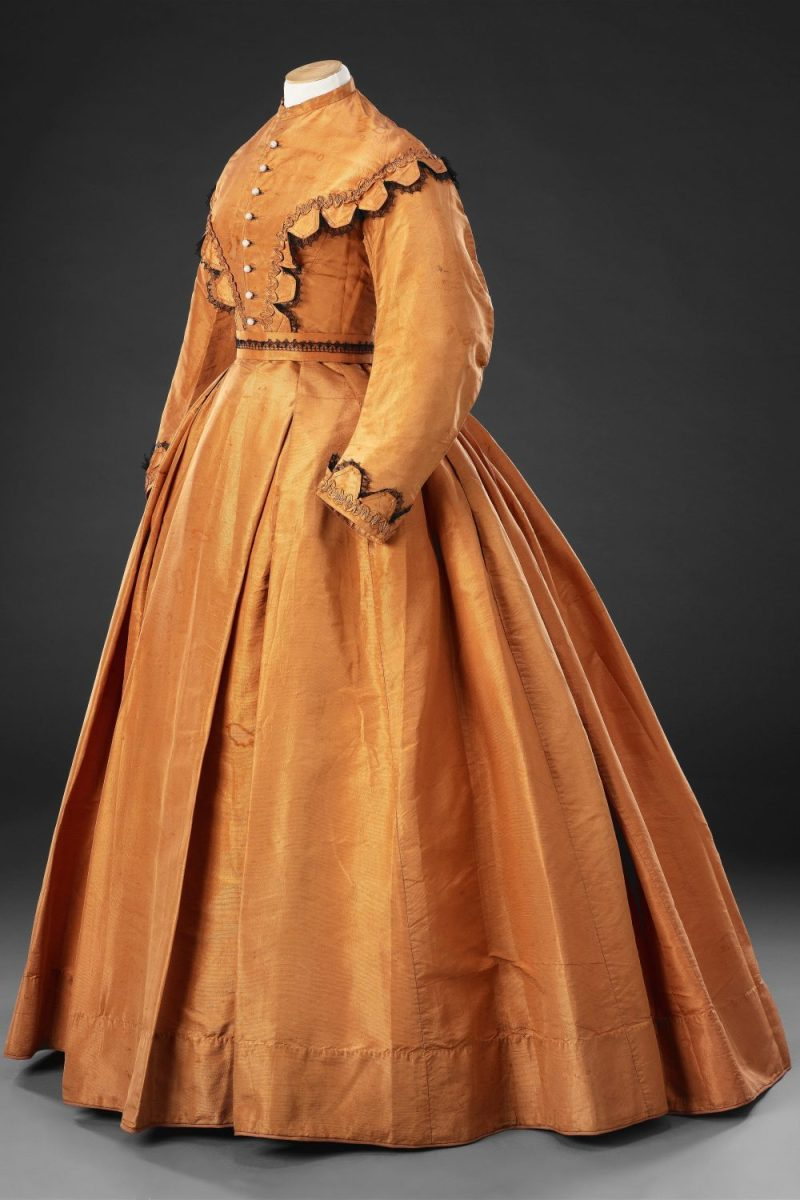 A day dress of plain, finely ribbed silk, with the minimum of trimming, demonstrates the characteristic features of the mid-1860s.