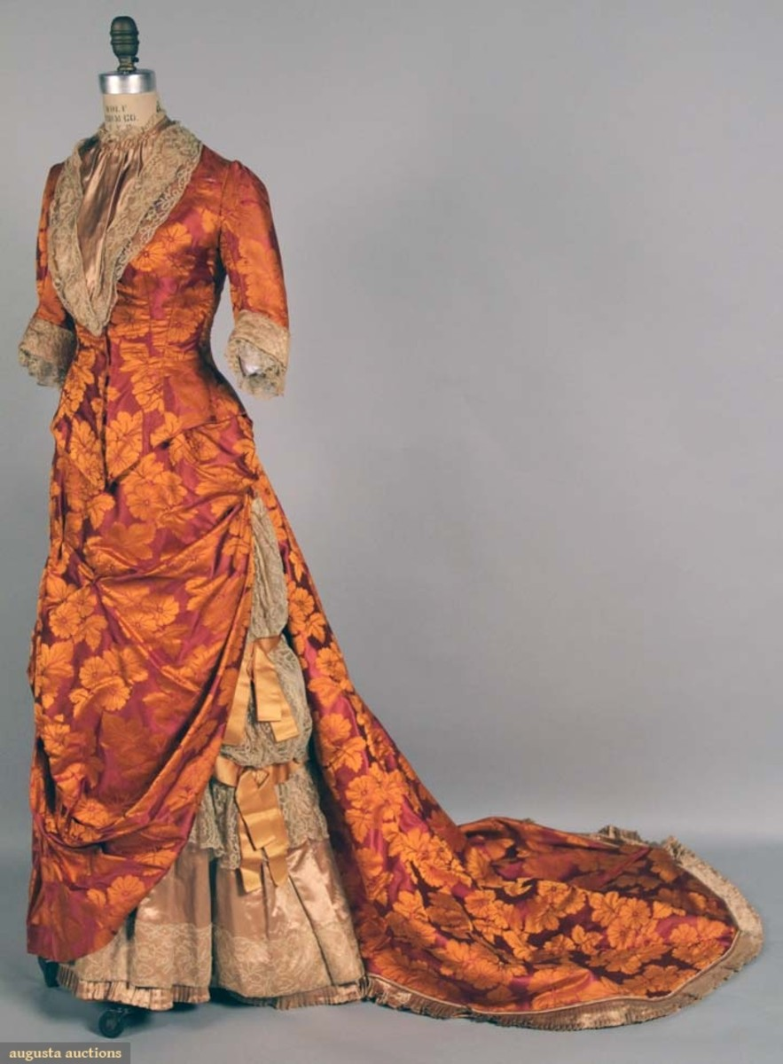 This two-piece silk brocade bustle gown from 1878-1883 gets a boost in both orange and purple flowers and foliage, and a trim of taupe satin and lace. This sold at auction for $480.