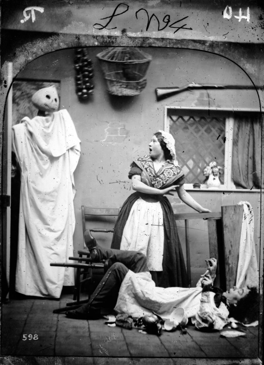 """Pumpkin Visitor,"" circa 1865. A white-caped figure wearing a pumpkin mask takes two people by surprise in their kitchen as part of London Stereoscopic Company's Comic Series."