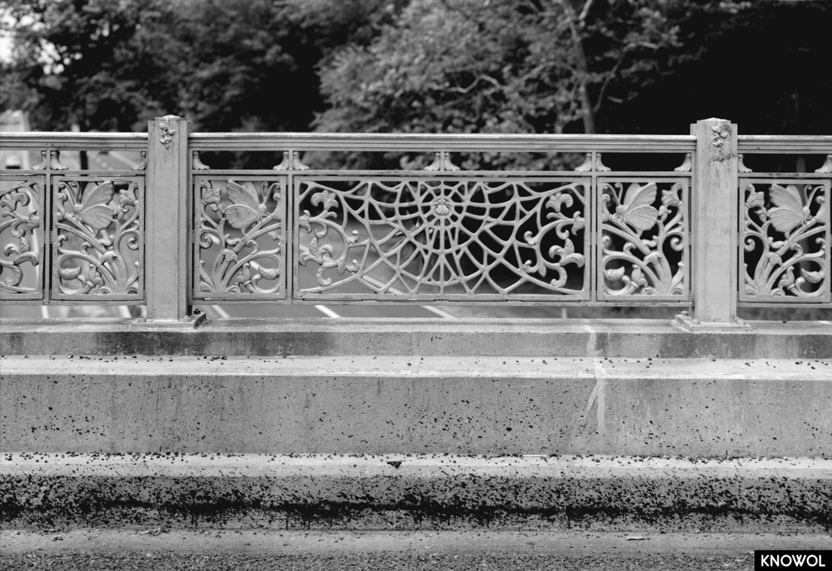 These is a close-up of the ornamental butterflies that adorn the pillars and decorative iron railing on Merwins Lane Bridge.