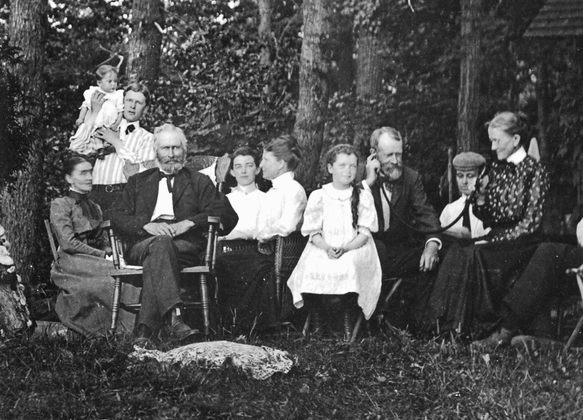 At a family gathering in 1903, Grandma yells in Grandpa's ear trumpet, at far right.