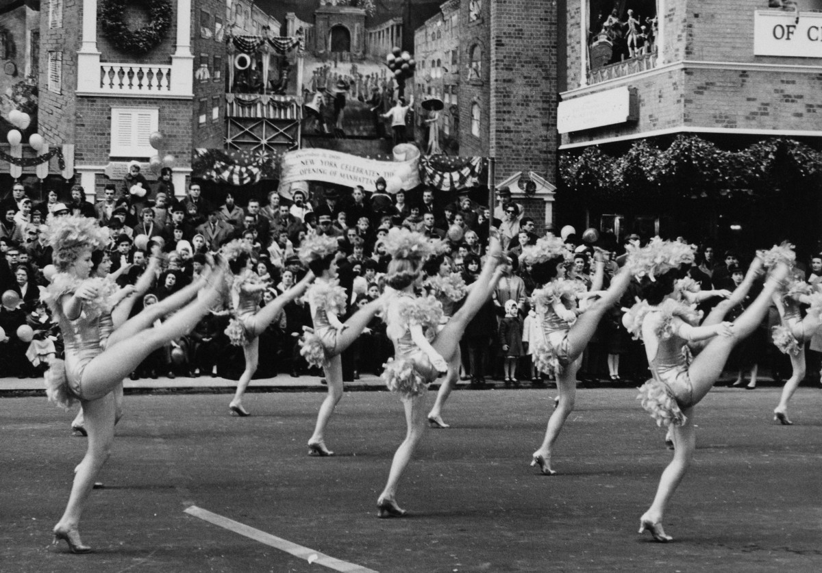 It wouldn't be a parade without some high-kicking ladies. This group was in the 1961 parade. A number of tableaux behind commemorate landmarks in the city's history.