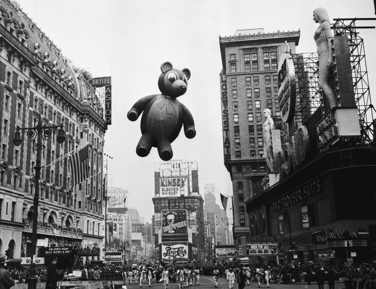 A teddy bear flies high and looks down on the crowd in 1949.