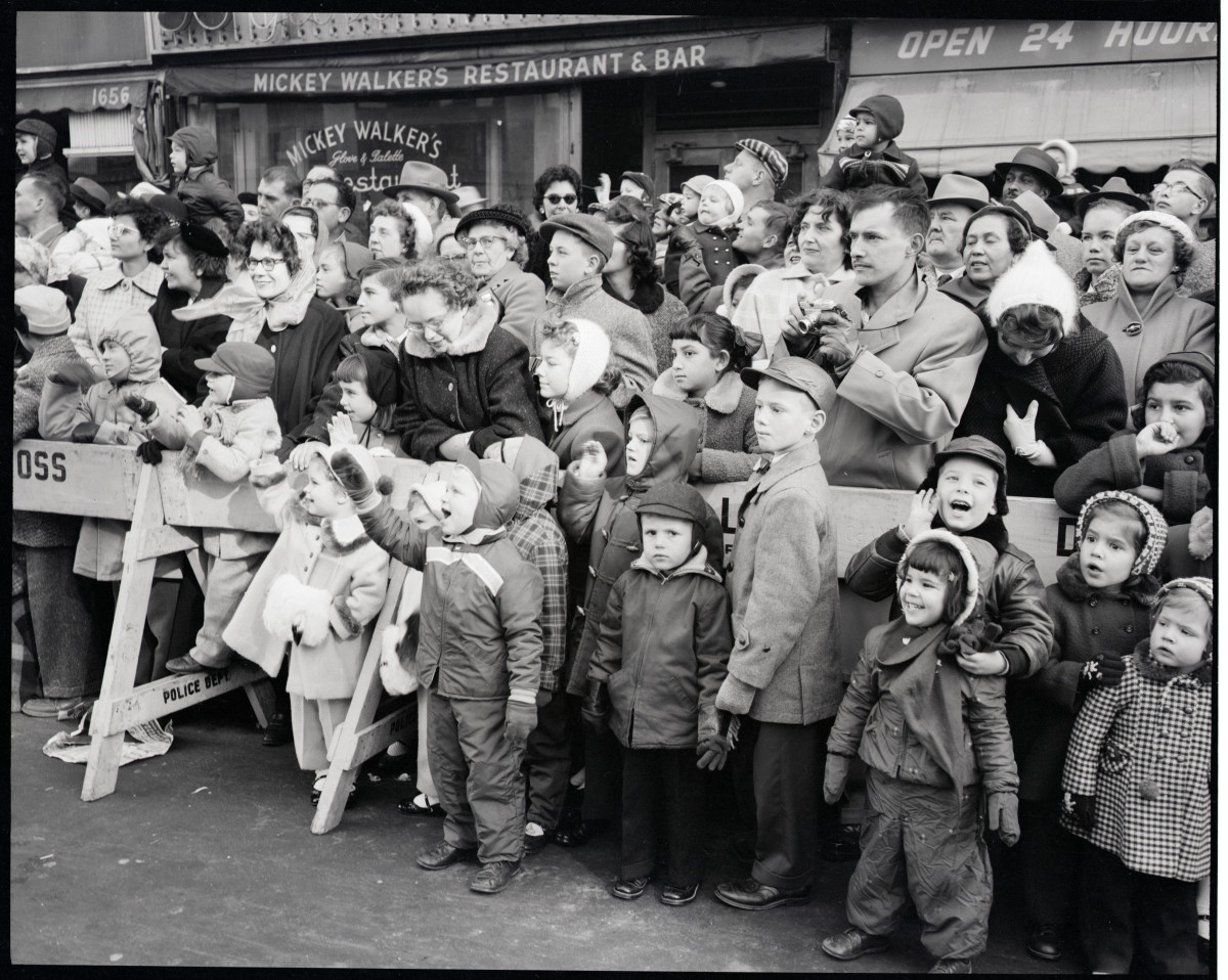 The crowd at the 1956 parade behind a police barricade, with children watching in the front.