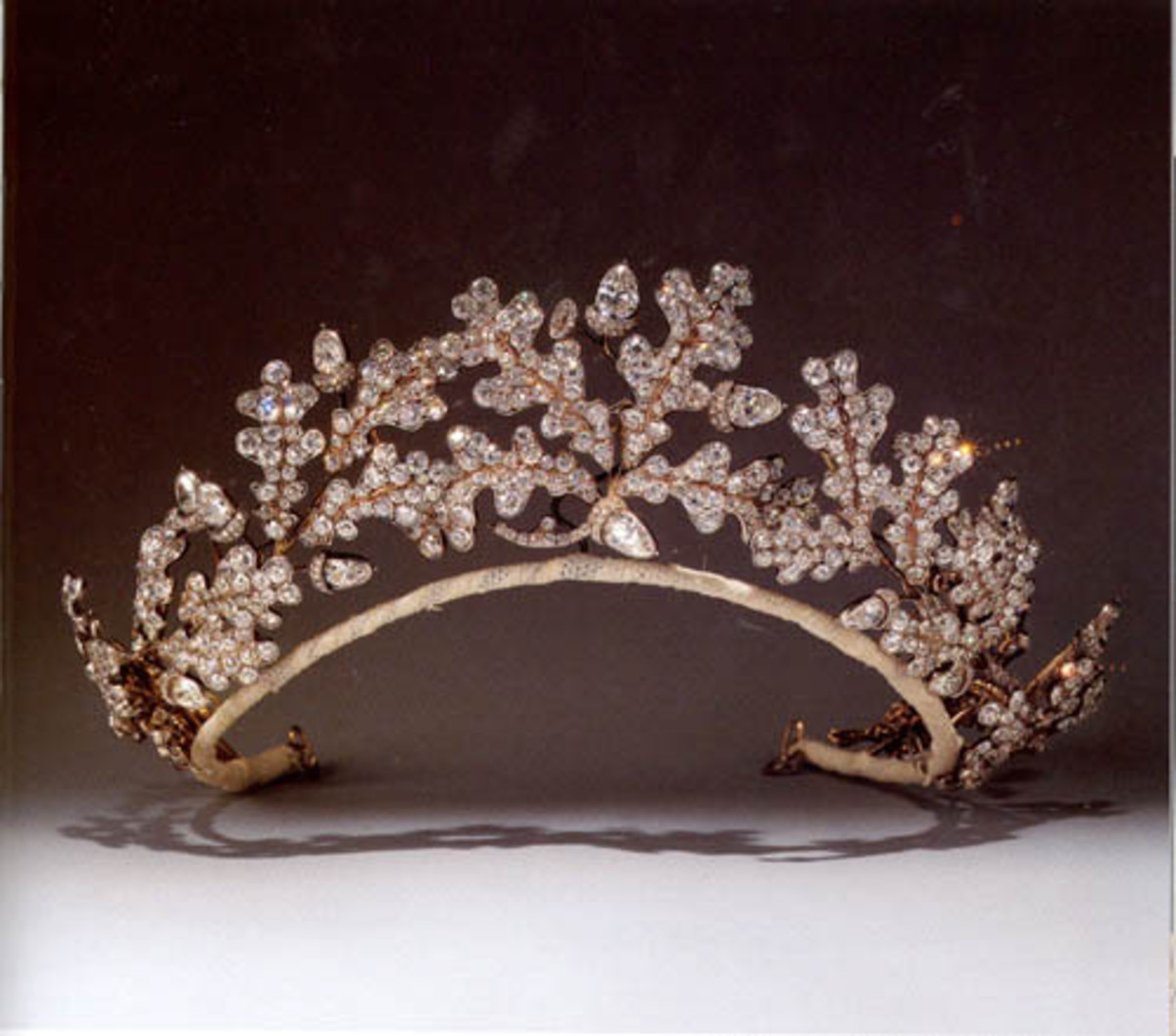 This tiara of oak leaves, acorns and hollow acorn cups was designed in the manner of ancient Greek jewelry, set with a profusion of brilliant-and rose-cut diamonds. It was made by Garrard after the Neo-Classical fashion of the early 19th century for the 15th Duke of Norfolk to give to his bride, Gwendolen Constable Maxwell, on their marriage in 1904.