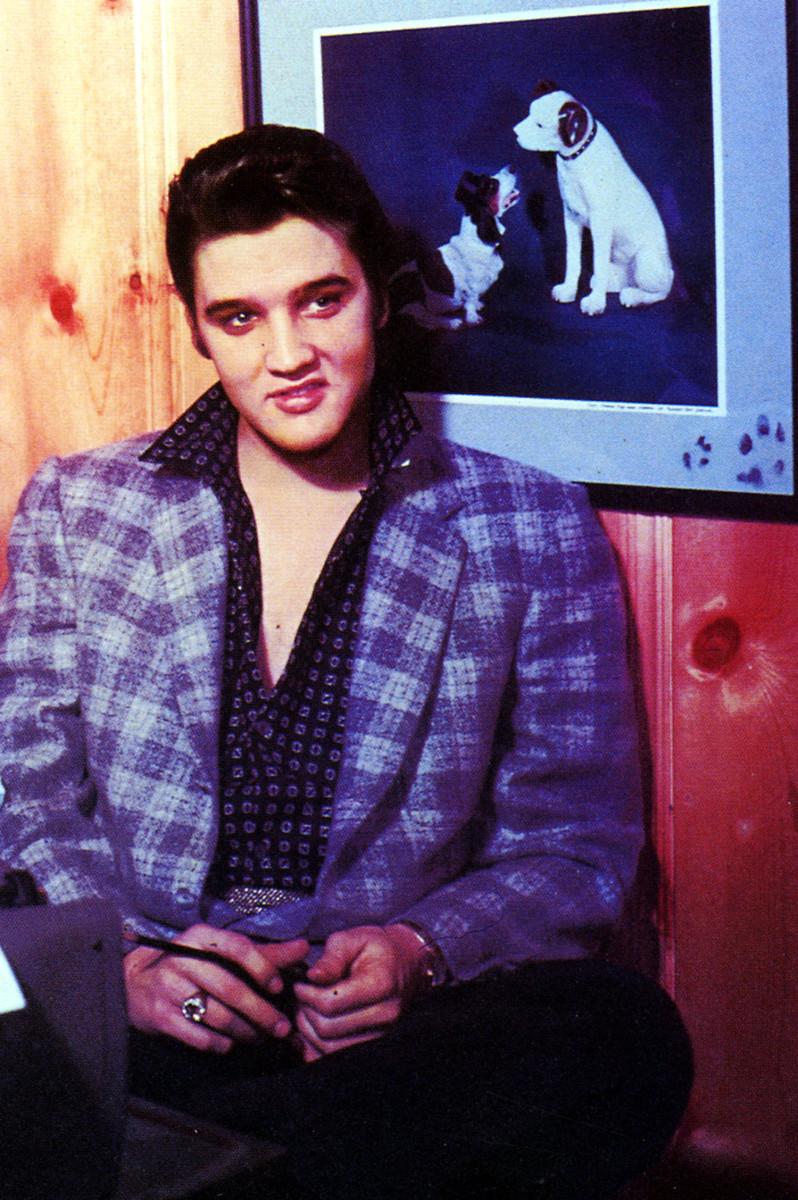 Elvis favored coats and jackets in unexpected colors, like this purple one, and with an open shirt, of course. Although the shirt has a clashing pattern, the future King works it. This photo is circa 1956-1957.