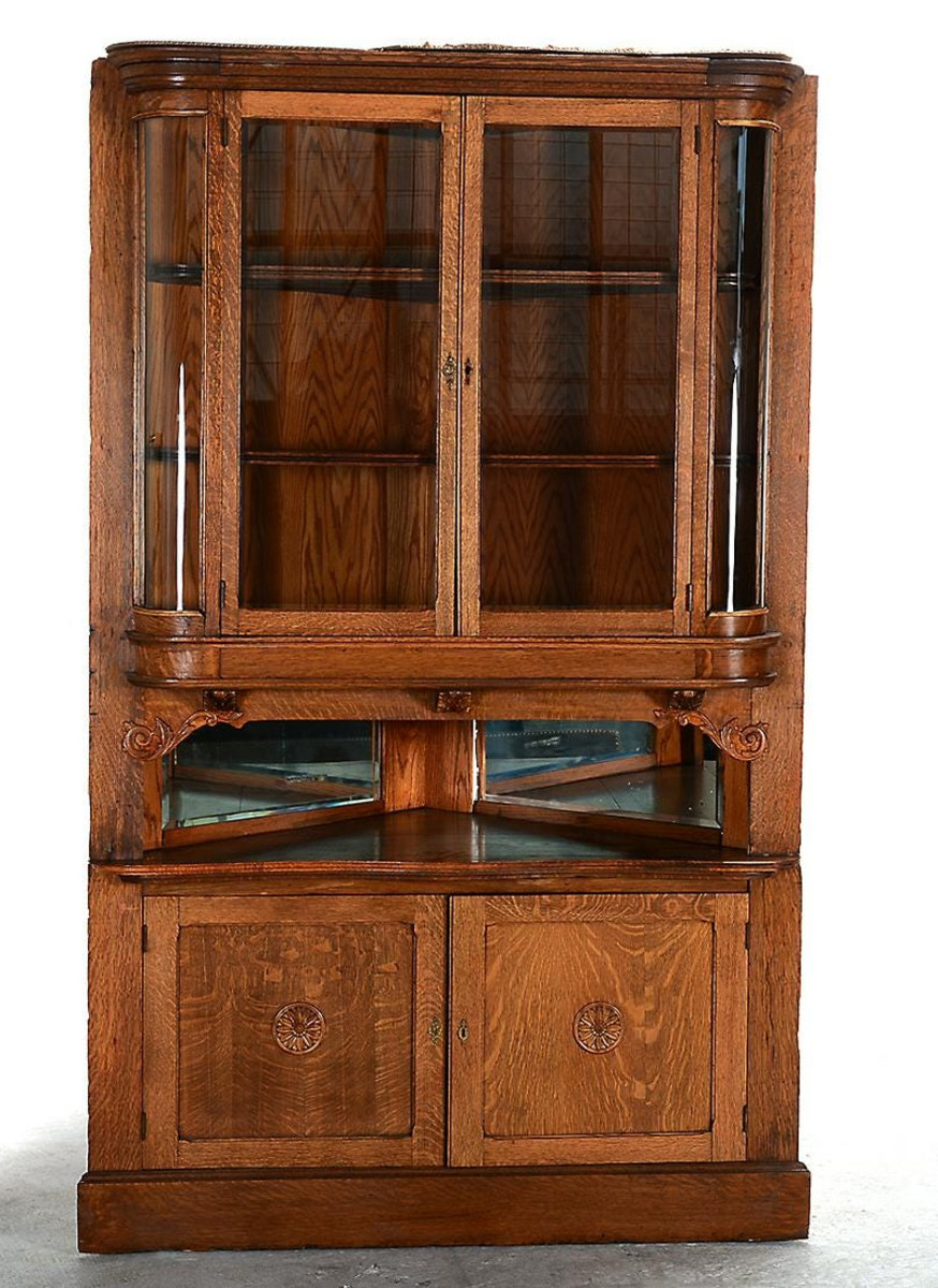 "Don't count out ""brown"" furniture yet. Golden oak was a top trend with ages 60-80. Golden oak corner cabinet, vitrine top on a two-door cabinet base, mirrored section in between the two, applied foliate carvings and rosettes; $226."