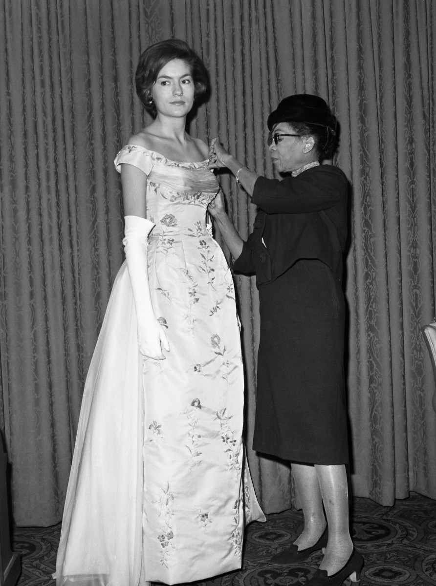 """Remaining in the background of the fashion world for 35 years in New York, Ann Lowe, had her first show in 1962. The designer, adjusting the bodice of a gown she designed and was worn by Alice Baker, has fitted most of the debutante and wedding dresses of the nation's top families, including Jackie Kennedy's. The nimble-fingered designer held her show in New York and her models were all """"silver spoon"""" girls - all old friends and devoted customers."""