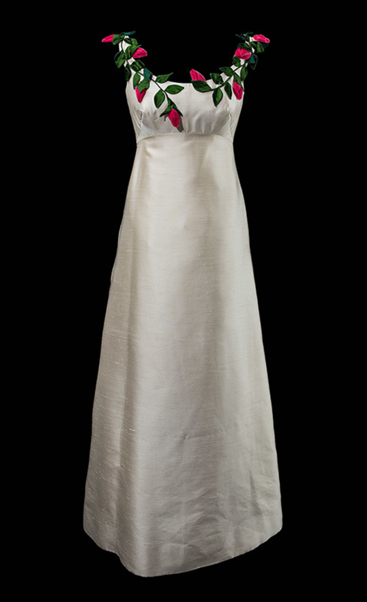 The dress Lowe designed for Duxbury's debutante ball. Flowers are a hallmark of Lowe's dresses, beautifully sculpted and delicately placed on her evening dresses. In this instance, red roses wind around the shoulder straps and bust of this gown.