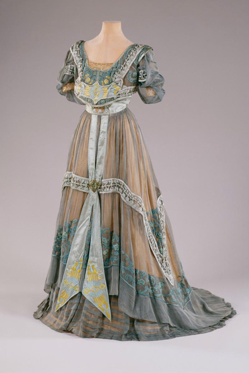 Evening dress designed by Callot Soeurs, Paris, circa 1907, turquoise silk moiré, turquoise cotton moiré, orange/gold silk crêpe, orange tulle, turquoise/gold silk cotton floss, turquoise/gold silk ribbon cord and  beading.