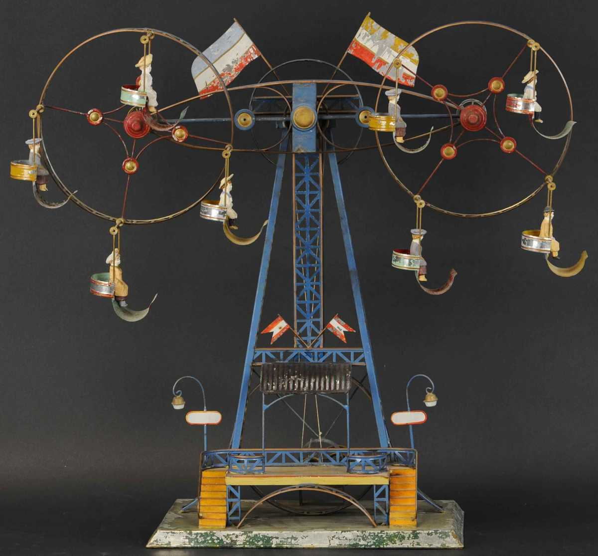 Mohr & Krauss Double Ferris Wheel, $138,000. A true museum-grade toy and a fantastic highlight piece of the Schroeder collection, this immense amusement features two large spinning wheels which also revolve around a central tower, original composition figures are seated in the suspended gondolas, and the toy can be hand cranked or powered by steam via a pulley system. Abby and Aaron were driving through a small town in Pennsylvania when they passed a closed barber shop with this toy prominently displayed in the front window. They spent the night and visited the shop the next morning. Aaron left with a haircut and Abby had this Double Ferris Wheel in her arms.