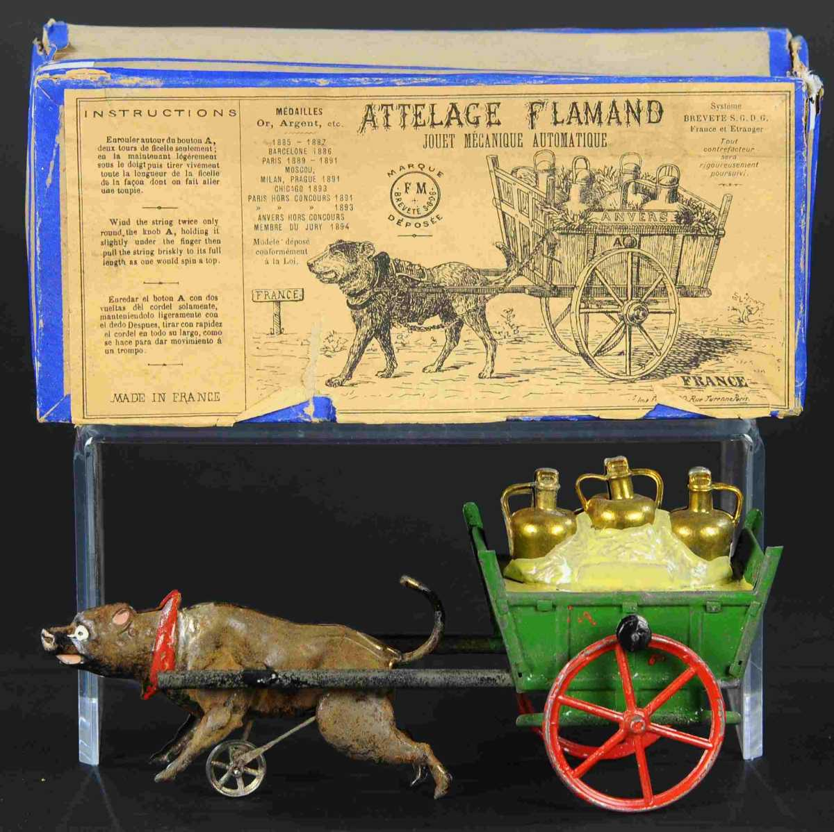 """A boxed Fernand Martin Flemish dog cart, circa 1894, France, $8,000. The """"Attelage Flamand"""" flywheel-driven cart contains copper milk cans and is pulled by dog. This is a scarce toy and the only boxed example Bertoia is aware of."""